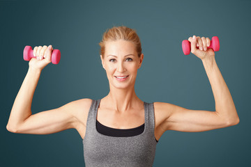 Toning her biceps. Portrait of an attractive middle age woman working out with dumbbells while standing at isolated background.