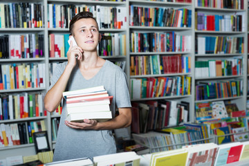 Boy holding books and talking on mobile phone in shop