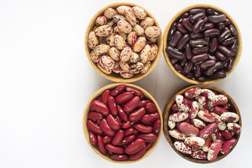 Four kinds of beans on white background. Top view.