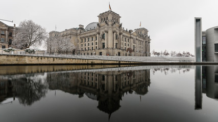 Berlin, Germany Winter The Reichstag is reflected in the cold waters of the Spree.
