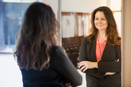brunette woman looking at herself in mirror