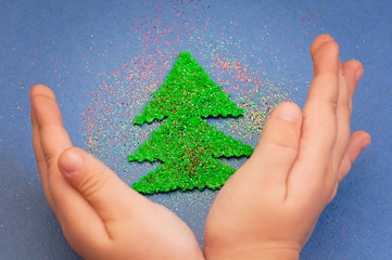 children's hands to protect Christmas tree cut from plush sprinkled with glitter