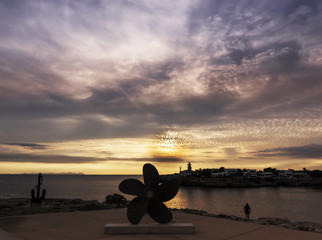 Amazing sunset over the sea with silhouette of propeller, anchor and  lighthouse in foreground. Menorca Island, Spain.