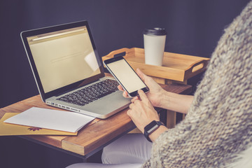 Close-up of laptop on wooden table and smartphone with blank screen in hands of a girl. Next is letter and a gold envelope.On table is cup of coffee. Woman checks email on smartphone.Girl uses gadget.