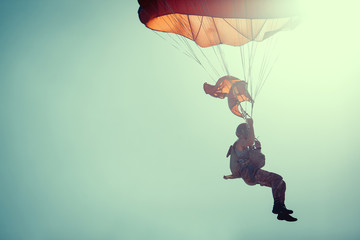 Skydiver On Colorful Parachute In Sunny Clear Sky.