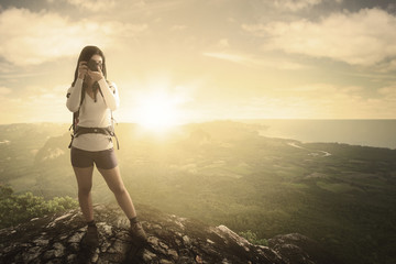 Female hiker and camera with valley view