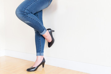 Women's jeans, black high-heeled shoes. White background
