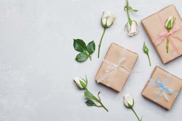 Gift or present box wrapped in kraft paper and rose flower on gray table from above. Flat lay styling. Copy space for text.