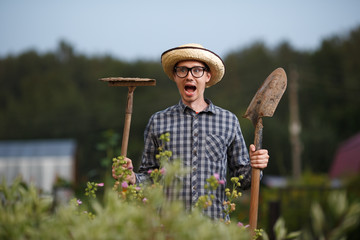 Funny farmer man with shovel and rake  open-mouthed