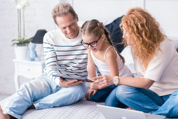 Cheerful little girl looking at the tablet with her grandparents
