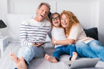 Laughing little girl hugging her grandparents