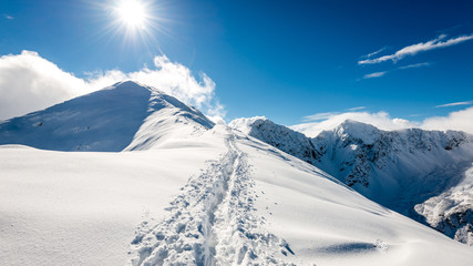 mountain tops in winter covered in snow with bright sun and blue