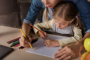 Lovely little girl drawing with her mother in the kitchen