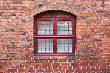 Old leaded painted wood window in an arched red brick wall in a townhouse in Elsinore, Denmark