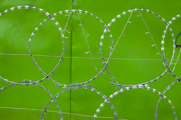 Razor wire and green sheet metal fence, Mandalay, Myanmar