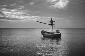 traditional fishing boat laying on the sea.cloudy sky.filtered image.selective focus.black and white color picture.HDR process