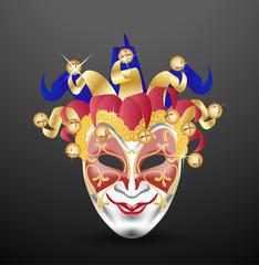 the joker face venetian mask with golden bells on dark backgroun