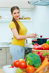 Smiling woman cooking in kitchen with fun.