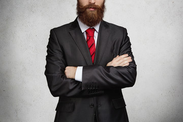 People, business and career concept. Cropped portrait of young Caucasian businessman wearing elegant suit and tie, standing in office with arms folded, demonstrating his confidence and power