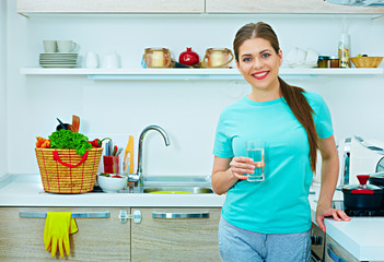 Smiling young woman holding water glass.