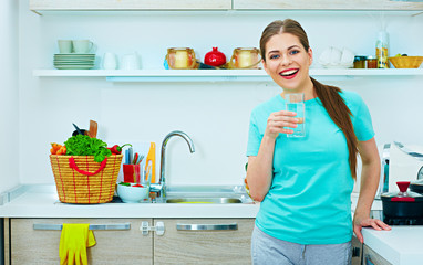 Smiling woman standing in kitchen  holding water glass.