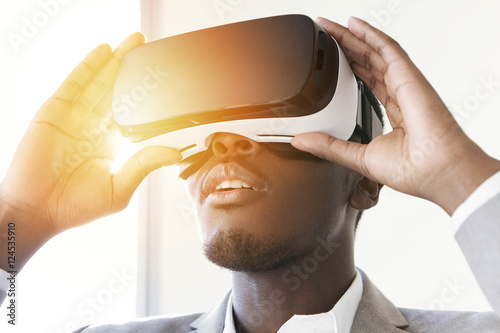 7b86ca04f03 Portrait of astonished African office worker or businessman using oculus  rift headset