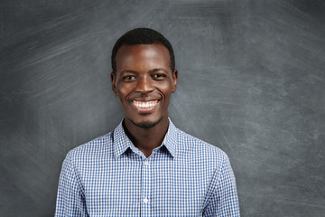 Human face expressions, emotions and feelings. Portrait of joyful African employee smiling with his white teeth, happy with big promotion and career growth. Success and achievements. Body language