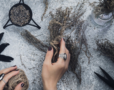 Directly above view of female hands making a bouquet of dried herb