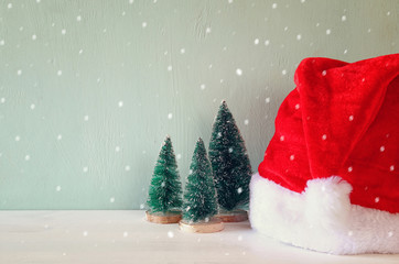 Image of christmas trees next to santa hat.