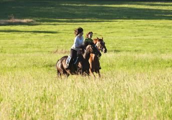 Foto op Aluminium Paardrijden Two Women Horseback Riding in a Landscape