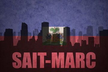 abstract silhouette of the city with text Saint-Marc at the vintage haitian flag