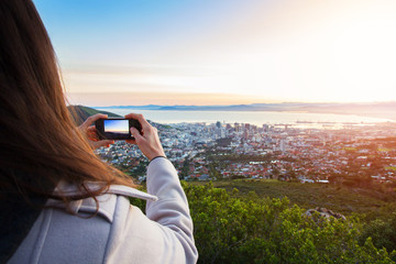 Tourist taking a photo on phone of Cape Town view