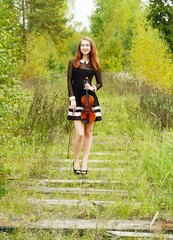 Girl with violin in the forest