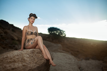 Pinup model in the swimsuit sitting on the rock with make up and hairstyle. Beautiful and sexy woman on the beach, vacation time on the sea.