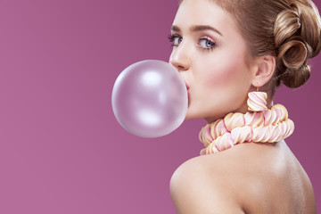Beautiful blonde woman blowing pink bubble gum. Fashion portrait.