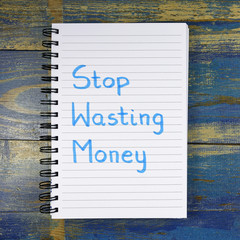 Stop Wasting Money text written in notebook on wooden background