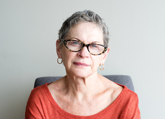 Portrait of older woman in orange top with glasses against neutral background