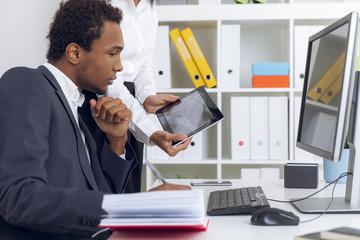 Boss is looking at secretary's tablet