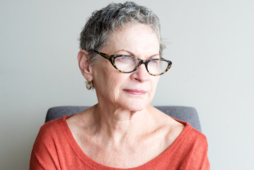 Older woman in orange top with glasses looking thoughtful against neutral background