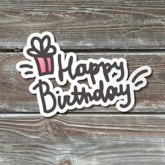 happy birthday handwritten text, paper sticker on realistic wood texture