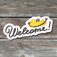 welcome, handwritten text, paper sticker on realistic wood texture