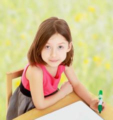 Little girl draws felt-tip pen on a white surface.