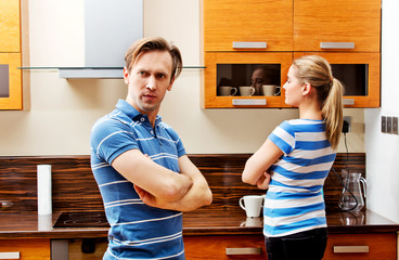 Quarreling couple standing in kitchen and don't talking with each other