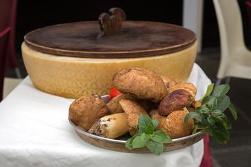Silver bowl of fresh raw Boletus edulis mushroom decorated with green leaves