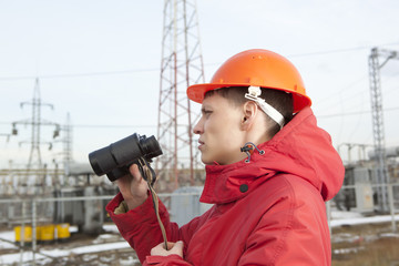 Engineer at Electrical Substation looks through a binoculars