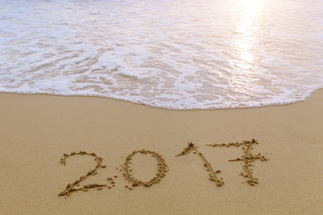 2017 written in sand of tropical beach, happy new year