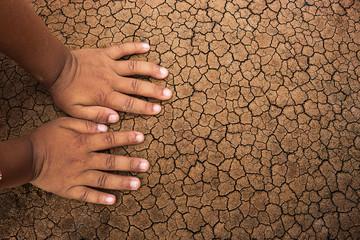 Children hands on the crack ground.