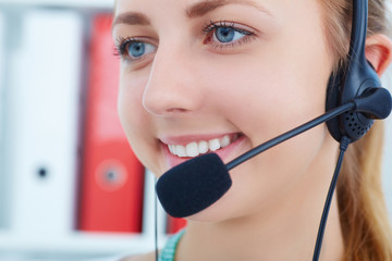 Female call center service operator at work. Portrait of pretty female helpdesk employee with headset at workplace. Effective and efficient business information, help and support concept