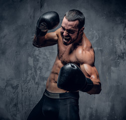 Aggressive shirtless boxer on grey background.