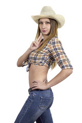The young girl in a cowboy wearing a cowboy hat, jeans and a plaid shirt mimics the firing of a gun. Isolated on white.